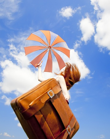 Redhead enchantress with suitcase jump in the sky. photo