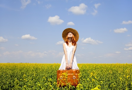 adult rape: Redhead enchantress with suitcase at spring rapeseed field.