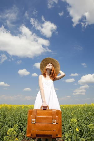 Redhead enchantress with suitcase at spring rapeseed field. photo