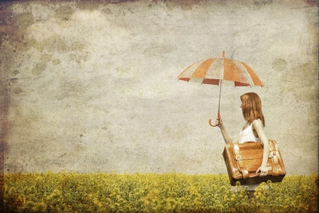 Redhead enchantress with umbrella and suitcase at spring rapeseed field. Photo in old image style. photo