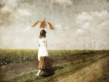 enchantress: Redhead enchantress walking near rapeseed field. Photo in old image style.