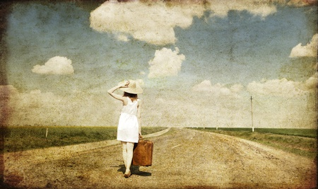 Lonely girl with suitcase at country road. Photo in old image style. photo