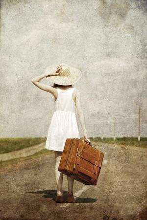 Einsames Mädchen mit Koffer auf Landstraße... Foto im alten Stil.