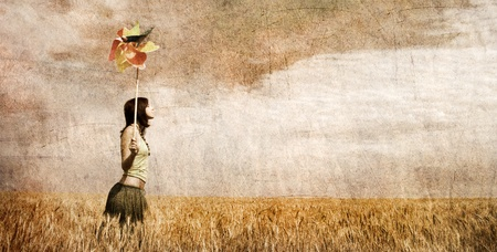 Girl with wind turbine at wheat field. Photo in old color image style. photo