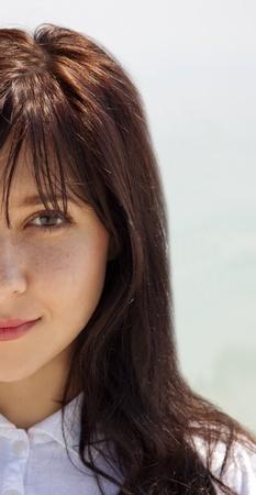 Half face portrait of  brunette girl. Outdoor photo.  photo
