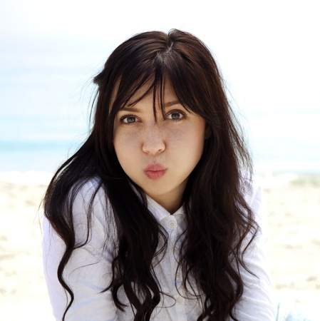 Young beautiful brunette girl lighten up at the beach in spring time. Outdoor photo.  photo