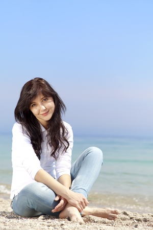 Young beautiful brunette girl at the beach in spring time. Outdoor photo.  photo