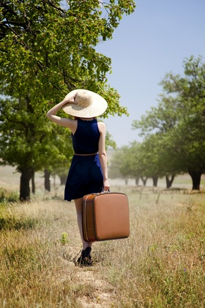 alone girl: Lonely girl with suitcase at countryside. Stock Photo