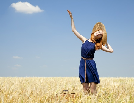 Redhead girl at spring wheat field. photo