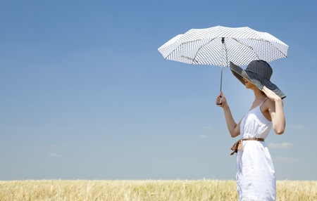 Redhead girl at spring field with umbrella.  photo