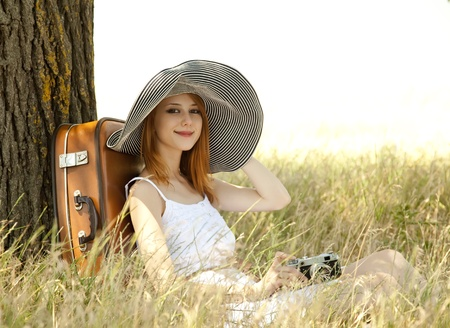 Redhead girl sitting near tree with vintage camera. Imagens
