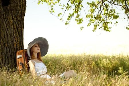 ropa de verano: Chica pelirroja en sombrero sentado cerca de �rboles en zonas rurales. Foto de archivo