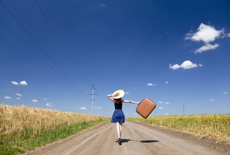 Lonely girl with suitcase at country road.  Stock Photo