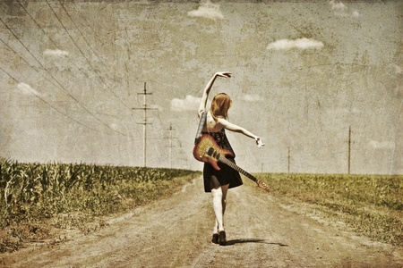 Rock girl with guitar at countryside. Photo in old image style. photo