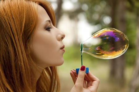to inflate: Redhead girl inflate soap bubble. Stock Photo