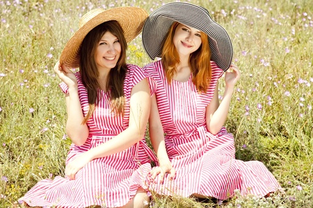 contryside: Two girls at contryside in red dresses. Stock Photo