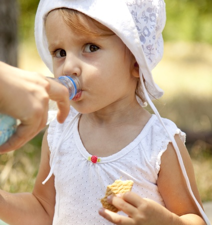 dring: Little girl dring water in the park. Stock Photo