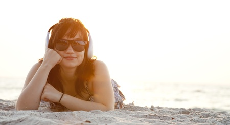 Beautiful brunette girl with headphones at beach sand in sunrise time. photo