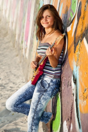 Beautiful brunette girl with guitar and graffiti wall at background. Stock Photo - 10568887