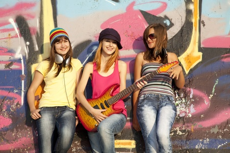 cute girlfriends: Three beautiful girls with guitar and graffiti wall at background.