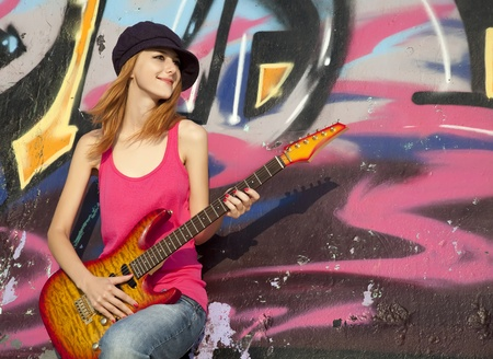 Beautiful red-haired girl with guitar and graffiti wall at background.