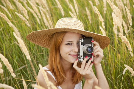 Redhead girl with old camera at outdoor. photo