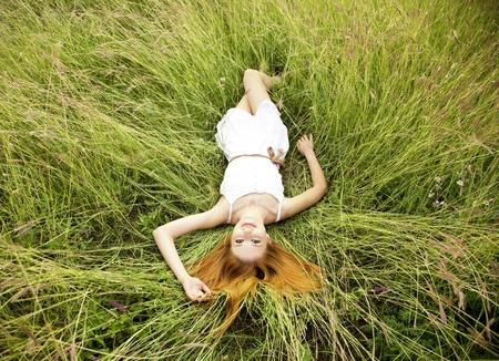 lying in grass: Hermosa ni�a acostada en la hierba.
