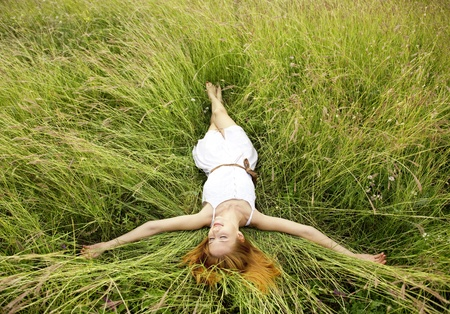 hands behind head: Beautiful girl lying down at grass.
