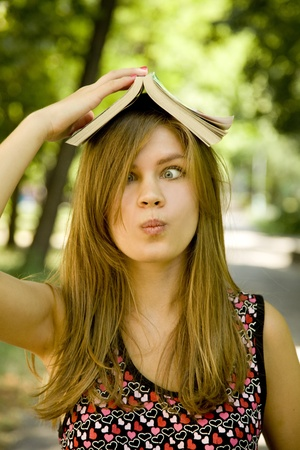 Blonde girl doing homework at the park. Stock Photo - 10663811