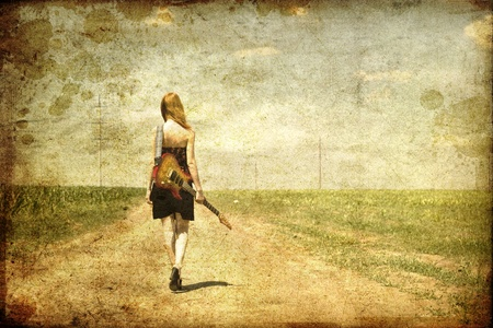 Rock girl with guitar at countryside. Photo in old image style. Stock Photo - 10663864