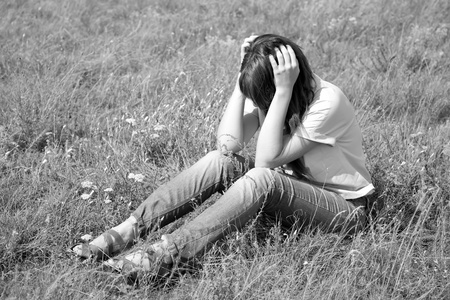 Sad girl at grass at countryside. Photo in black and white image style. photo