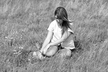 Sad girl at grass at countryside. Photo in black and white image style.