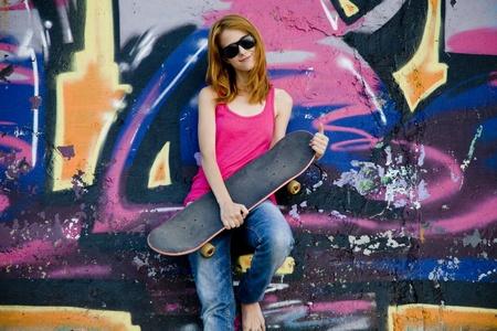 Style girl with skateboard near graffiti wall. photo