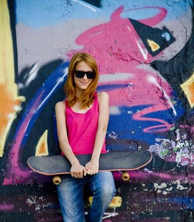 wand graffiti: Style-M�dchen mit Skateboard-Graffiti-Wand in der N�he.