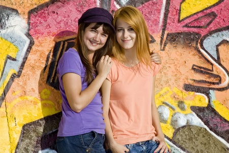 Two girlfriends near graffiti wall Stock Photo - 10663881