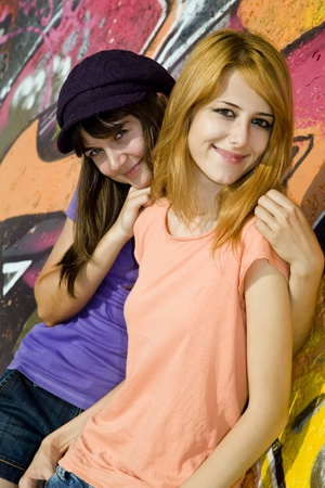 Two girlfriends near graffiti wall Stock Photo - 10663868