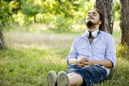 Man sitting on green grass with headphones. Stock Photo - 10663793