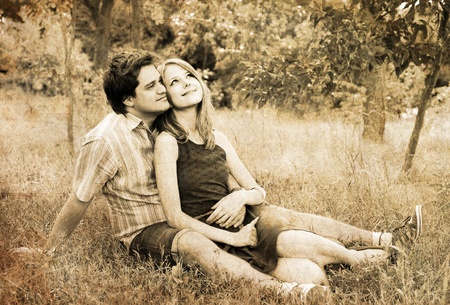 closeness: Young couple in love outdoors. Photo in old image style.