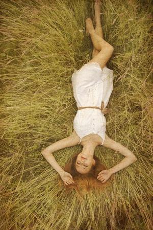 Belle fille couchée à l'herbe. Banque d'images