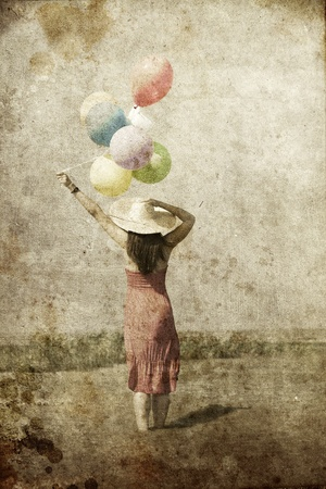 Brunette girl with colour balloons at coast. Photo in old color image style. photo