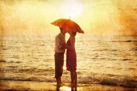 parejas de amor: Pareja bes�ndose bajo el paraguas en la playa en el atardecer. Foto en el estilo de la antigua imagen. Foto de archivo