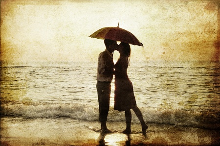 love kiss: Couple kissing under umbrella at the beach in sunset. Photo in old image style. Stock Photo