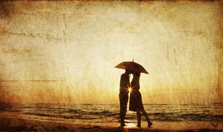 novios besandose: Pareja bes�ndose bajo el paraguas en la playa en el atardecer. Foto en el estilo de la antigua imagen. Foto de archivo