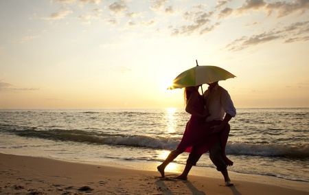 Couple kissing under umbrella at the beach in sunset. Stock Photo - 10689944