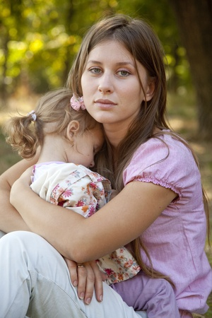 children sad: Sad little girl and mother in the park