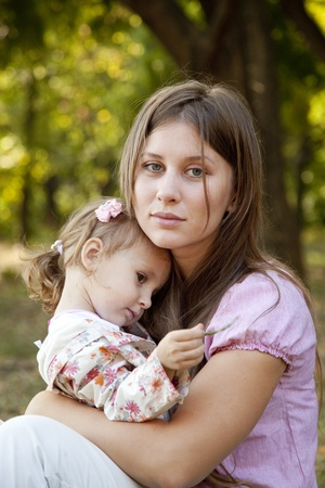 causal: Sad little girl and mother in the park