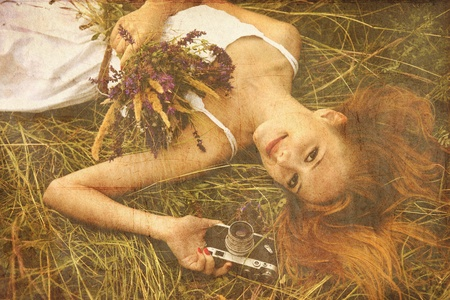 Redhead girl with vintage camera at outdoor. photo
