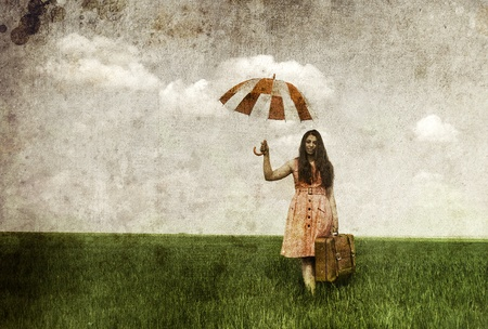 enchantress: Brunette enchantress with umbrella and suitcase at spring rapeseed field. Photo in old image style.