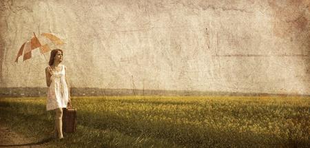 Redhead enchantress walking near rapeseed field. Photo in old image style. photo