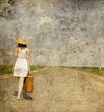 Lonely girl with suitcase at country road.. Photo in old image style.